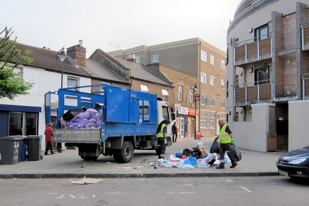 Men tossing rubbish into their truck.