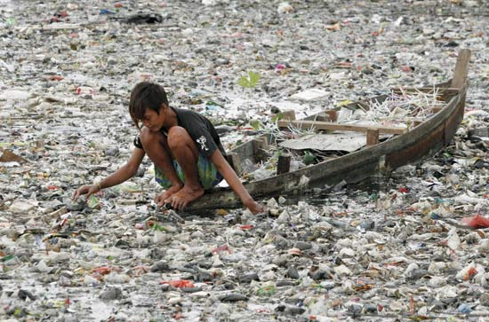 A boy surrounded by plastic rubbish.