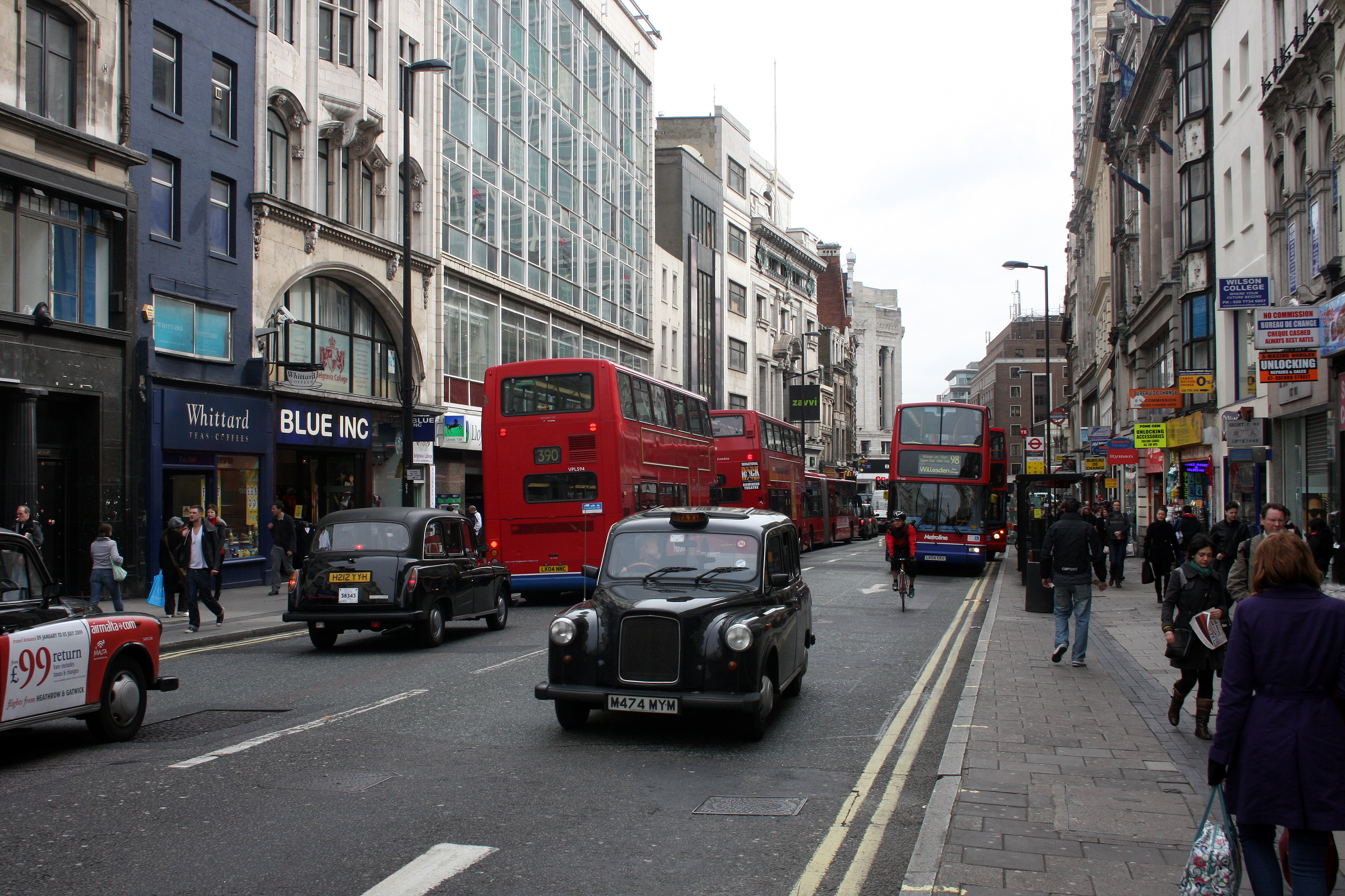 Buses and taxis on a London street.